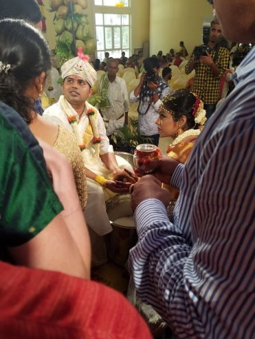 Here's the bride and groom holding the coconut.