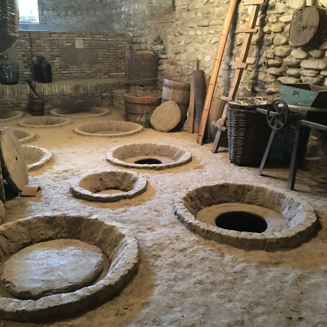 The buried clay 'kvevri' for fermenting wine. Each kvevri holds around 800 L of wine, so these things are big.