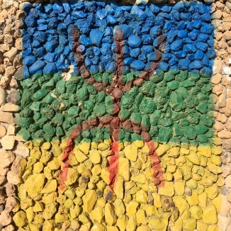 The Berber flag painted on a rock wall.